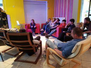 Jugendliche und junge Erwachsene sitzen im Stuhlkreis und hören der Referentin zu.