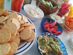 Zu sehen sind Gemüsesticks, Dips und Cracker in Schüsseln.